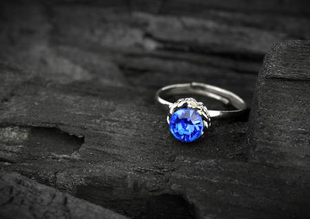 Anello gioielleria dormivamo con SAPPHIR blu su sfondo scuro del carbone, soft focus Archivio Fotografico - 44877236