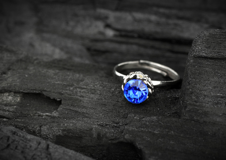jewellery ring witht blue sapphir on dark coal background, soft focus