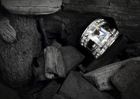 ジュエリー リング暗い石炭の背景に使って大きなカラフルなダイヤモンド