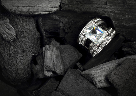 jewelry ring witht big colourful diamond on dark coal background