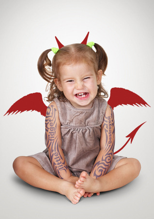 Portrait of bad child with tatoo and devil horns, disobedient baby concept
