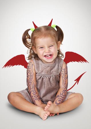 Portret van slechte kind met tatoo en duivel horens, ongehoorzaam kind begrip Stockfoto