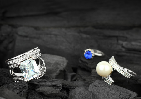 Few jewelry rings with brilliants, gems and pearl on black coal background, soft focus