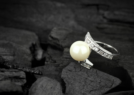 jewelry background: jewelry with brilliant and pearl on dark coal background, soft focus Stock Photo