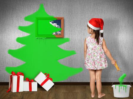 prankster: Funny child dressed Santa hat, draws Christmas tree on wall at home, xmas concept Stock Photo