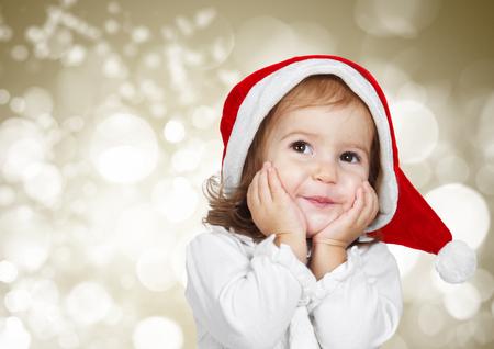 christmas hats: Funny child dressed santa hat, on bokeh background Stock Photo