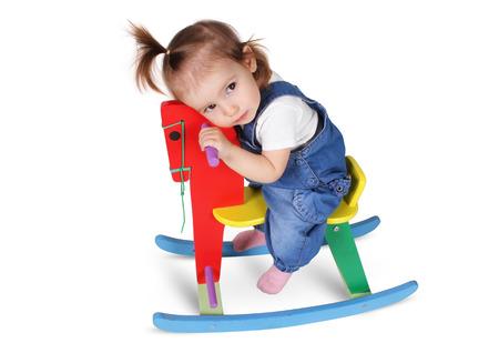 Grappig doordachte kind droomt op stuk speelgoed paard, geïsoleerd op wit