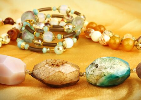 bead jewelry: jewelry gems on golden background Stock Photo