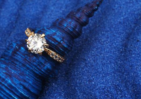 macro juwelen ring met grote diamant op blauwe schelp en zand achtergrond