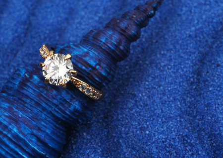 ringe: Makro von Schmuck Ring mit großen Diamanten auf blauem Seashell und Sand Hintergrund Lizenzfreie Bilder