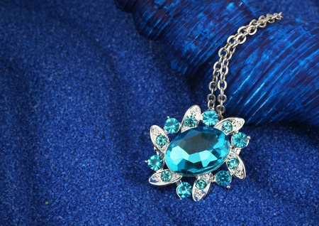 copyspace: Jewelry pendant with gems on blue background with copy-space