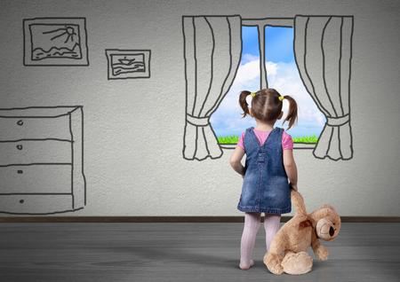 Muchacha del niño con aspecto de oso de juguete en la ventana dibujada, el concepto de sueño