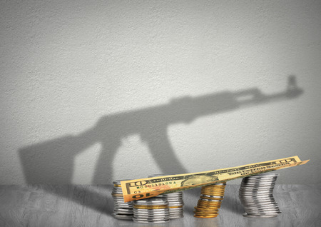 financing terrorism concept, money with weapon shadow