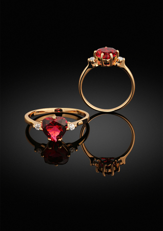 precious stone: jewelry ring with heart-shaped gem on black background with reflection Stock Photo
