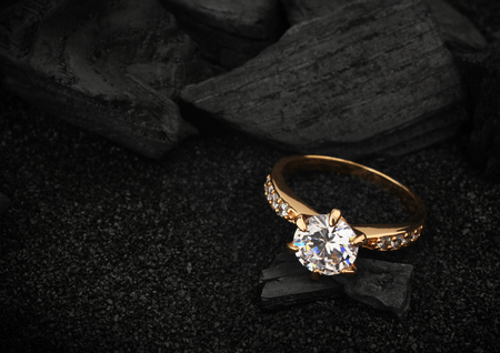 ringe: Schmuck Ring abgesprochen großen Diamanten auf dunklen Kohle und schwarzem Sand Hintergrund
