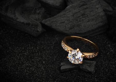 Sieraden ring met grote diamant op donkere steenkool en zwarte zand achtergrond Stockfoto