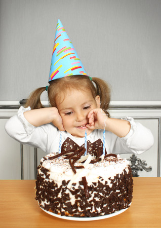 eat smeared: Portrait of funny little girl with birthday hat and cake