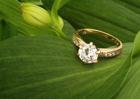 Pierścień Jewellry z dużym diamentem na tle zielonych liści