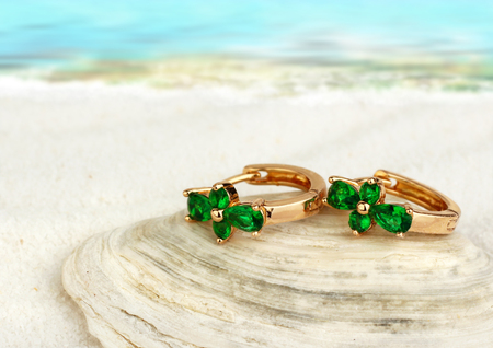 jewellry: Jewellry earrings with emerald on sand beach with, soft focus Stock Photo
