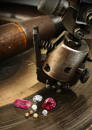 collet: Faceting gemston, big diamond with jewelery equipment on background.
