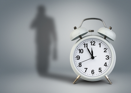 Clock with businessman shadow, time management concept Stock Photo