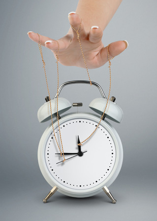 Hand puppeteer manipulating alarm clock, time management concept