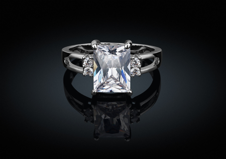 jewelry ring with big square diamond on black background with reflection Фото со стока