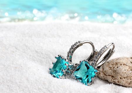 Sieraden oorbellen met aquamarijn op zandstrand achtergrond, zachte focus