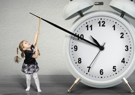 deter: Little child girl pulling hand clock, time management concept