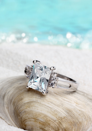 Jewelry ring with diamond on sand beach background, soft focus