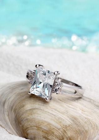 exposición: Joyería anillo con diamante en la playa de arena de fondo, enfoque suave
