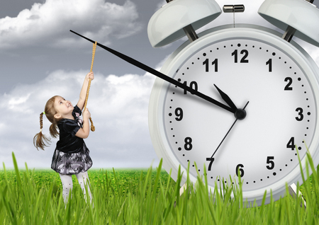 Little child girl pulling hand clock, time stop concept