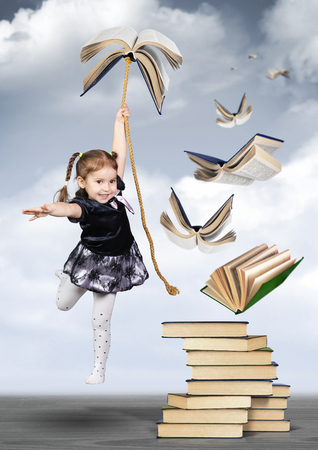 Education concept , child girl fly on book