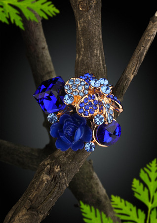 Jewellery ring as flower on twig, dark background Stock Photo