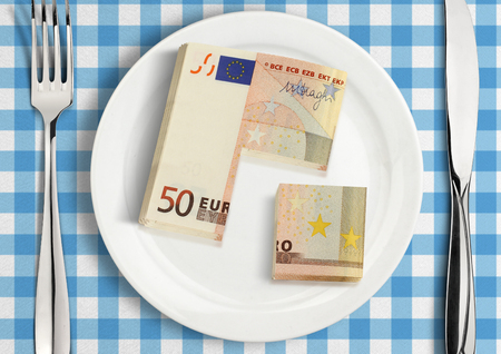 payday: Cut money on plate, financial share concept Stock Photo