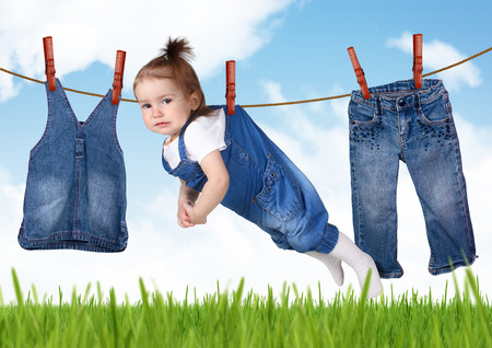 muddy clothes: confused housework concept, Funny child hanging on clothesline