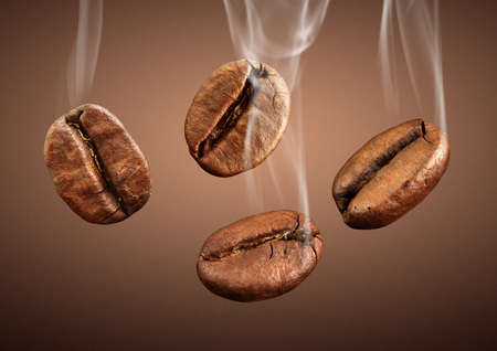 falling coffee beans with smoke on brown background Stock Photo