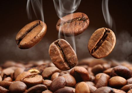 Macro of falling coffee bean with smoke on brown background