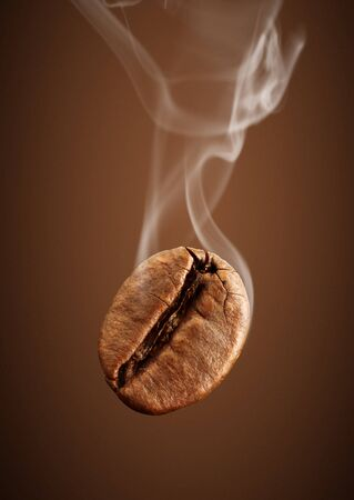 falling coffee bean with smoke on brown background Stock Photo