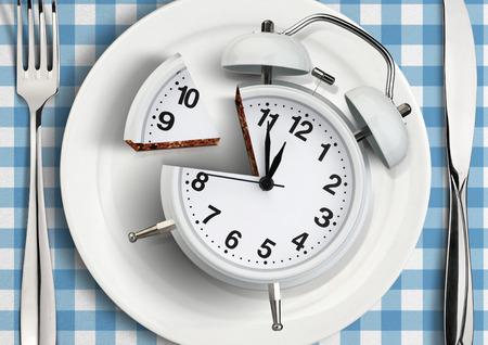 Concetto di tempo al pasto, tagliare l'orologio sul piatto. Archivio Fotografico - 73871670