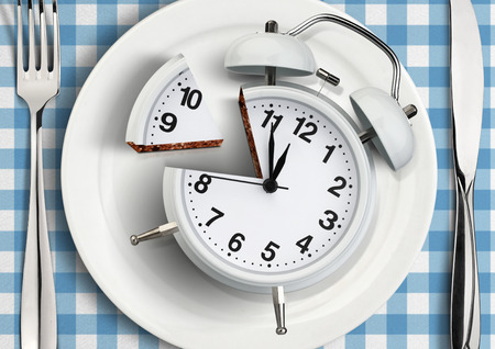 Time to meal concept, cut clock on plate. Stock Photo