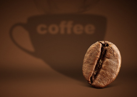 Coffee concept, bean with cup shadow on brown