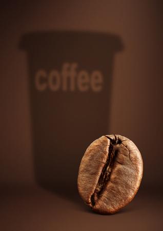 Coffee concept, bean with paper cup shadow on brown  Stock Photo