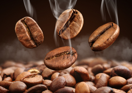 Macro falling coffee bean with steam on brown background Stock Photo