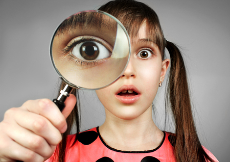 surprised girl, searching  with magnifying glass Stock Photo