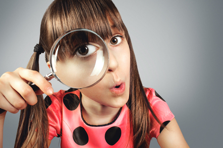 inspector kid: amazed child girl looking through magnifying glass, searching concept