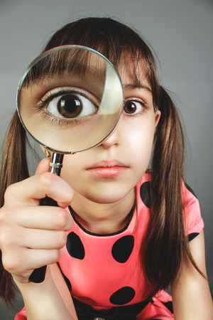 laughable: little child girl searching  with magnifying glass