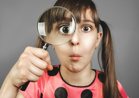 bewilderment child girl looking through magnifying glass