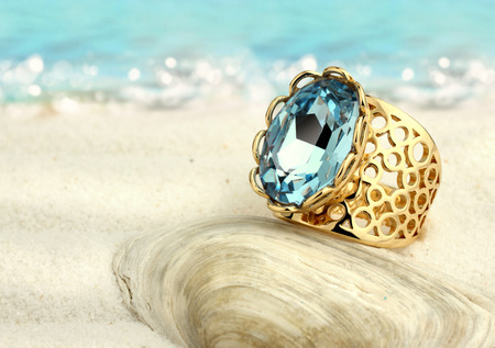 Golden ring with aquamarine on summer sand beach