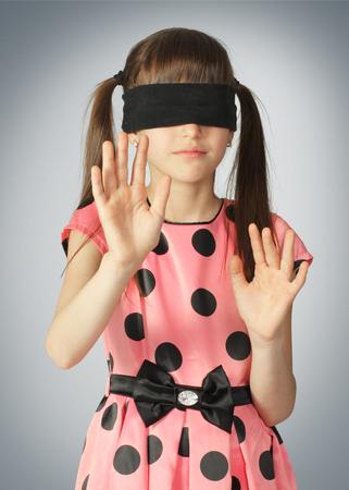 Niño con los ojos vendados, concepto ciego sobre fondo gris